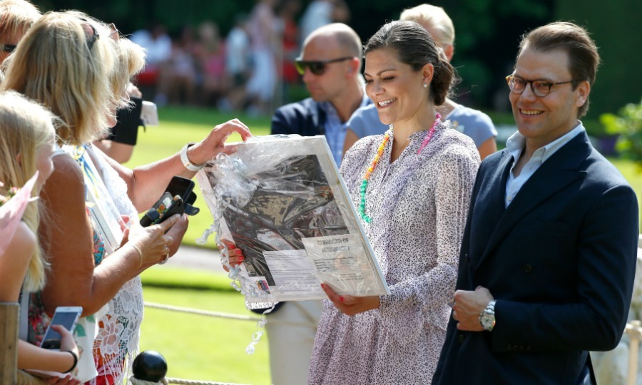 The royal couple had a blast accepting gifts from Swedish fans. 