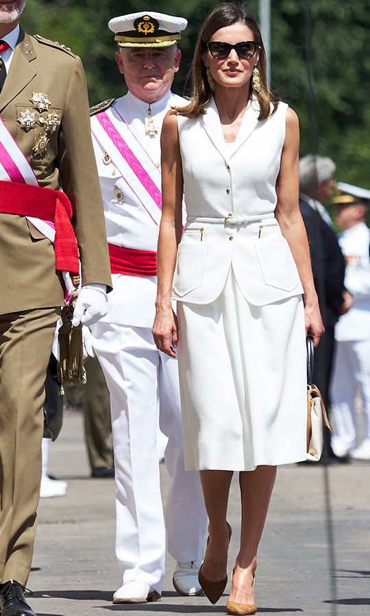 Debuting what's sure to become a wardrobe staple by Spanish designer Felipe Varela on July 18, Queen Letizia looked cool as can be in the matching white dress and pocketed waistcoat. The skinny belt gave us major Meghan Markle vibes, and the stylish monarch paired the ensemble with Carolina Herrera accessories (brown suede sling back heels, a Camelot colour-block handbag and oversized sunnies) while visiting the Central Academy of Defense in Madrid.