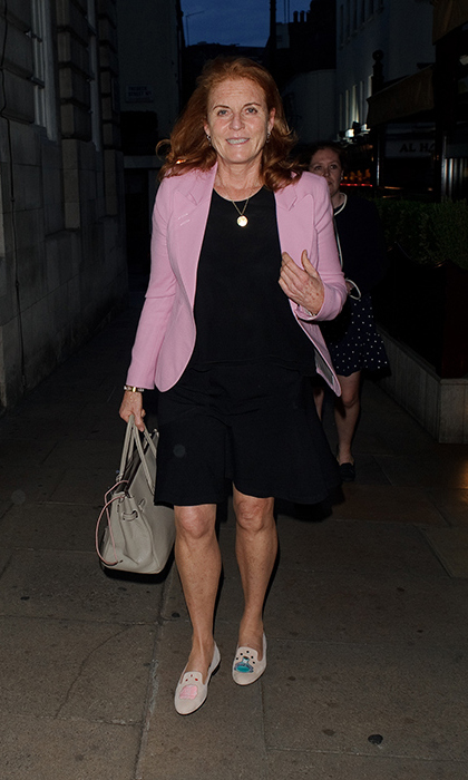 Sarah, Duchess of York headed to one of her favorite London hotspots on Friday evening (July 20) – private member's club Lou Lou's in Mayfair - and wore a fabulous outfit for the occasion. The former wife of Prince Andrew stepped out in a simple but chic little black dress, which she glammed up with a pastel pink blazer which gave the whole look a gentle pop of colour. The Duchess carried a dove-grey tote bag and accessorised with a gold pendant. However, what REALLY made her outfit stand out was her choice of footwear – her pink pumps by French Sole are certainly unique. The £200 slipper-style loafers were designed in a light pastel hue and feature embroidered motifs on the front – on one shoe there was a sewn image of a bottle that said 'Drink Me' on it and on the other a badge which read 'Eat Me' was seen. These slogans are from the Lewis Carroll classic Alice in Wonderland and are part of the brand's collaboration with blogger Alice Naylor-Leyland.