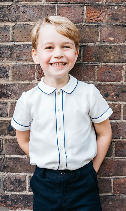 The prince turned five on Sunday (July 22) and Kensington Palace released a new portrait in celebration. In the photo, George shows off his megawatt smile, wearing the same outfit he donned for Prince Louis' christening – a white Amaia Kids shirt with blue piping and navy shorts, his blond hair styled in a sweet side part. The third-in-line to the throne looks up with his big brown eyes, likely at the photographer – or maybe his parents, Prince William and Duchess Kate, who could very well be making funny faces behind the camera to make him smile!