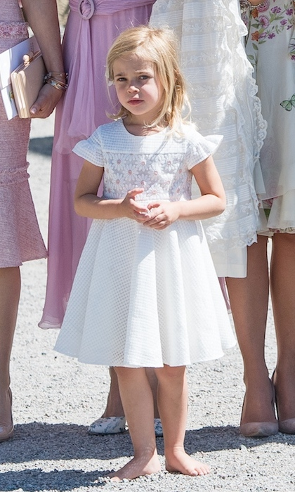 Leonore, age 4, was the picture of comfort after kicking off her shoes during her baby sister Princess Adrienne's christening on June 8 2018, before joining her family for portraits outside the palace's chapel.  
