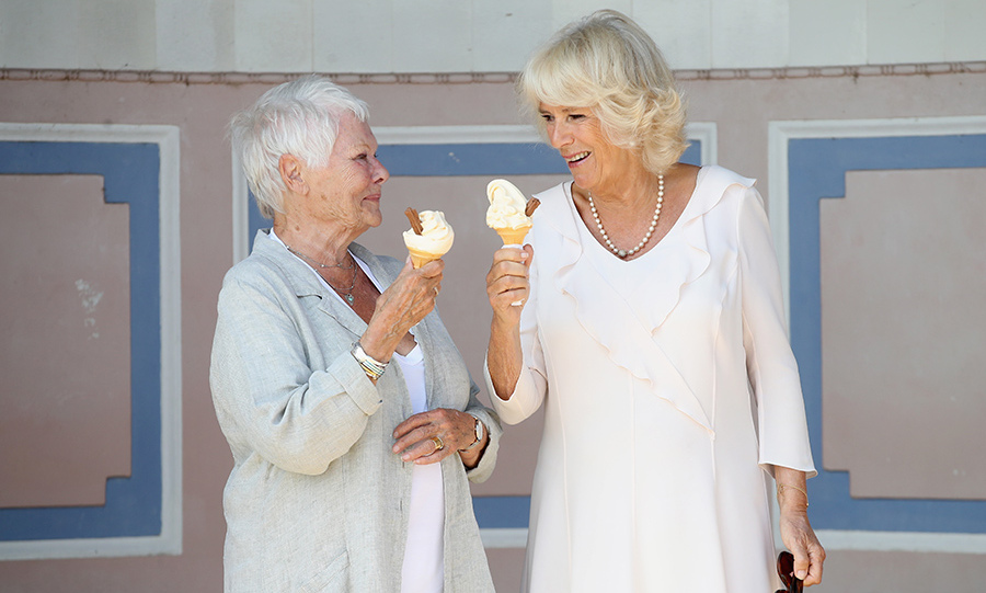 Dame Judi Dench and Camilla, Duchess of Cornwall cooled off in the Isle of Wight with a couple of ice cream cones. The actress, who has played both Queen Victoria and Queen Elizabeth, joined the royal on the private beach of Queen Victoria's former home, Osborne House, on July 24. Dame Judi, who is patron of Friends of Osborne House, looked lovely in a white blouse and grey linen topper while Camilla donned a white dress with ruffled detailing and a pearl necklace for the occasion.