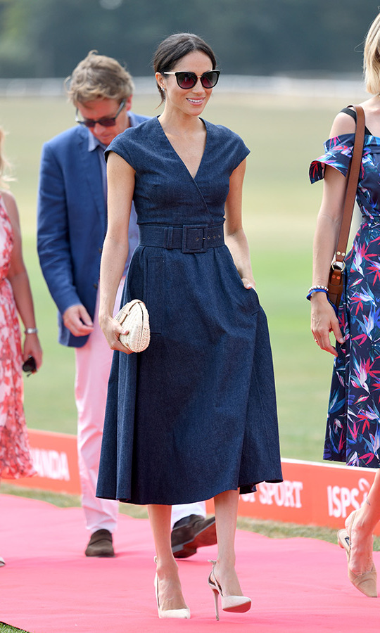 Carolina Herrera was responsible for the stunning dress that Meghan wore to Prince Harry's Sentebale ISPS Handa Polo Cup in Windsor on July 26. The navy number featured a cap sleeve and v neck with a fuller pocketed skirt. She traded the slim belts she'd been favouring for a wide one, showing off her tiny waist. The royal slipped into her favourite Deneuve Bow Pumps in a creamy hue and topped off the look with a raffia clutch and chic sunnies.