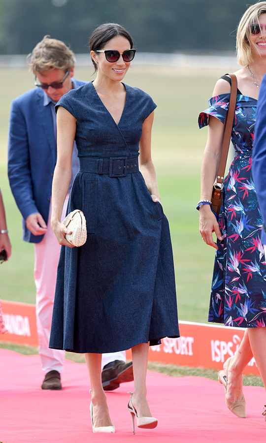 Meghan slipped into the most stylish polo look for her day on the sidelines. The denim Carolina Herrera dress features a v neckline and cap sleeves with a wide belt and full skirt. The best part? Pockets! The 36-year-old's favourite Aquazzura Deneuve Bow pumps anchored the look.