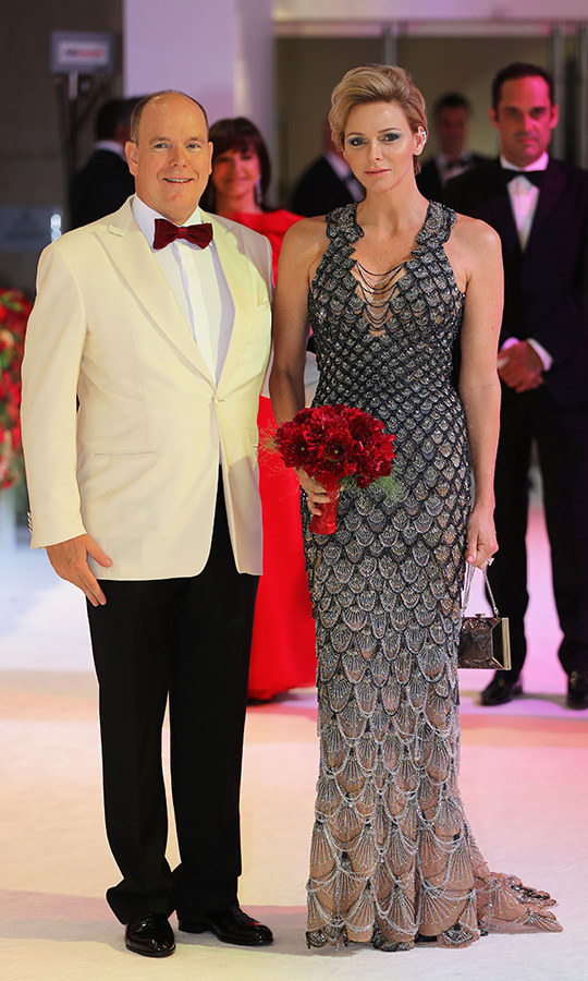 Princess Charlene joined Prince Albert at the  70th Red Cross Gala looking spectacular in a scalloped Versace gown with draped beading at the neckline. The fashion-forward royal accessorized with a box clutch, striking diamond ear cuff and metallic blue eyeshadow. Her husband looked dapper in a  cream jacket, black pants and a burgundy bow tie.