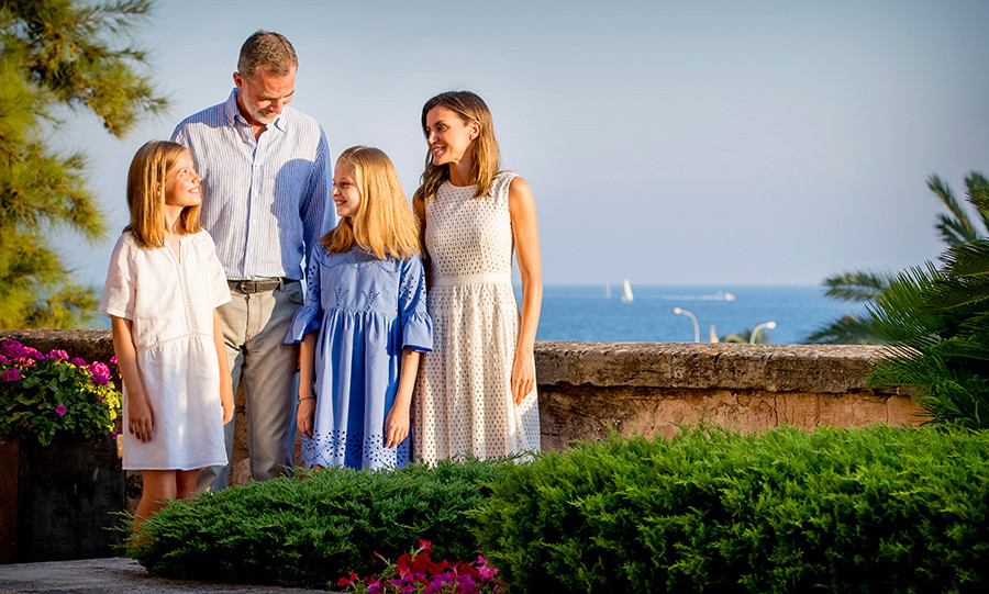 We're booking tickets to Mallorca as we speak! The Spanish royal family and their lush surroundings were picture-perfect as they posed for a sweet series of snaps while on their annual summer holiday in Palma de Mallorca, Spain.