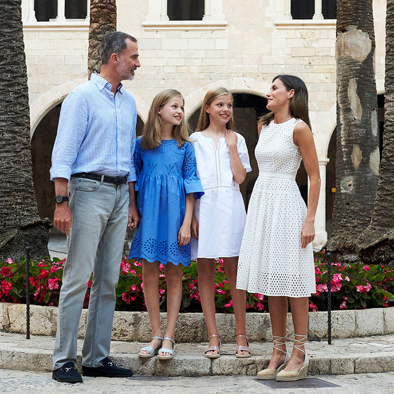 During their summer photocall in Mallorca, the Spanish royal family was perfectly in sync in their blue and white ensembles. King Felipe looked relaxed in grey jeans, a blue linen shirt and black driving shoes, while his stylish wife Queen Letizia turned to Hugo Boss for her mesh dress with a nipped waist. She anchored the look with espadrilles by Spanish brand Mint & Rose. Princess Leonor, 12, looked darling in a cornflower blue dress by Zara with a scalloped hemline and keyhole detailing, while her sister Princess Sofia donned a white drop-waist Massimo Dutti dress also with keyhole embellishments. Both  daughters wore metallic sandals by Sarah World featuring a small wedge heel.