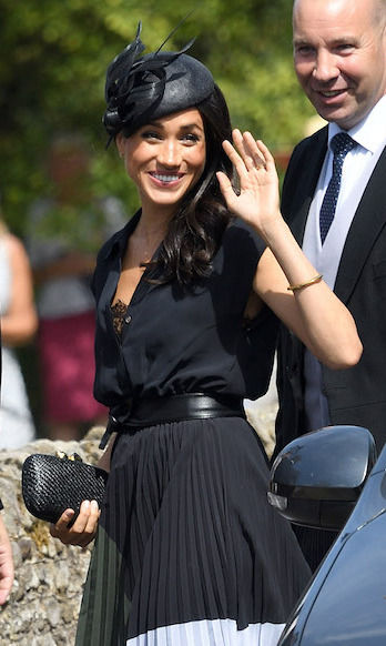 Straying from her look as of late, Meghan kept her brunette locks in loose curls under her hat.