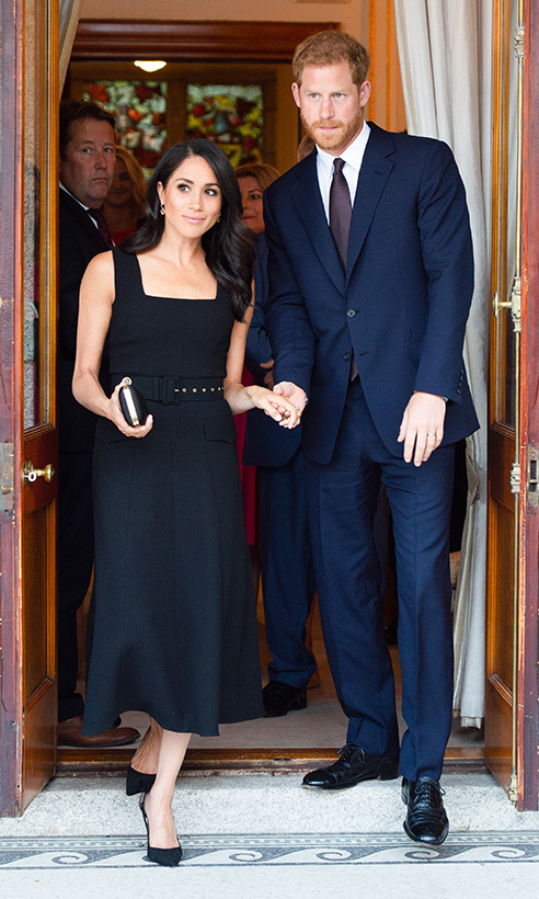 Prince Harry delicately held his wife Meghan's hand as they arrived at a starry reception in Ireland during their first official overseas visit. The couple looked dapper as ever, she in a black Emilia Wickstead dress and he in a navy suit and brown tie.