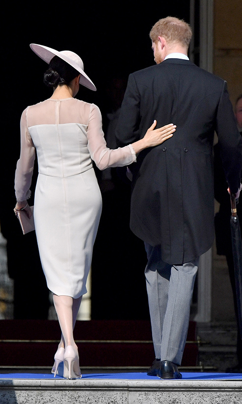 Meghan placed a tender hand on Prince Harry's back at the couple's first official engagement following their dreamy royal wedding. The just-married pair stepped out for a garden party at Buckingham Palace celebrating Prince Charles' 70th birthday. 