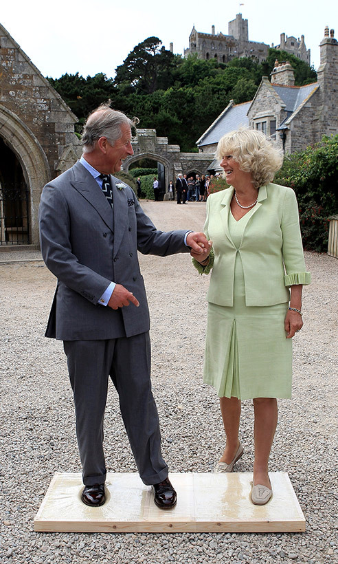 On their annual two-day trip to Cornwall in July, the Prince of Wales and Duchess of Cornwall shared a sweet moment holding hands as Charles helped Camilla onto the cast that would imprint their feet at St Michael's Mount.