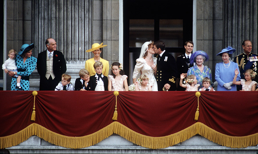 The Duke and Duchess of York gave fans the moment they'd been waiting for as they kissed on the balcony after their wedding surrounded by fellow members of the Royal Family. The little bridesmaid standing in front of Sarah is Zara Tindall! 