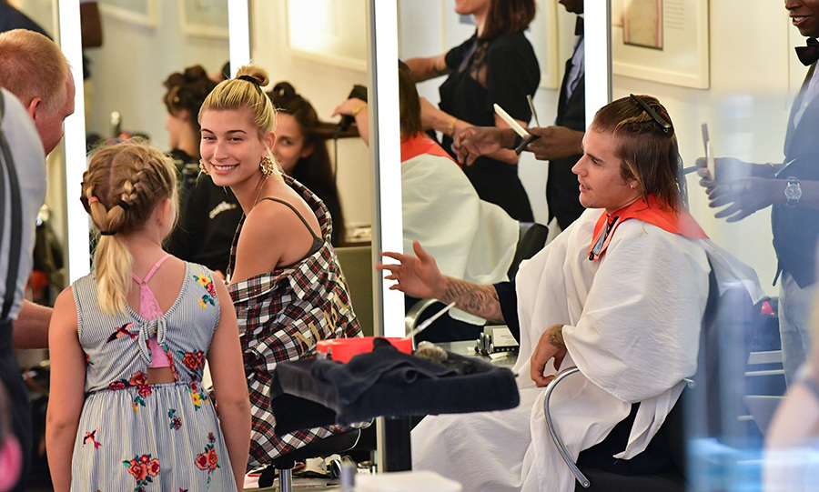 Newly engaged lovebirds Hailey Baldwin and Justin Bieber popped into New York's Cutler Hair Salon on Aug. 8 to tame the singer's wild locks. The duo was in high spirits and chatted with young fans while the Canadian star had his shoulder-length hair trimmed. 