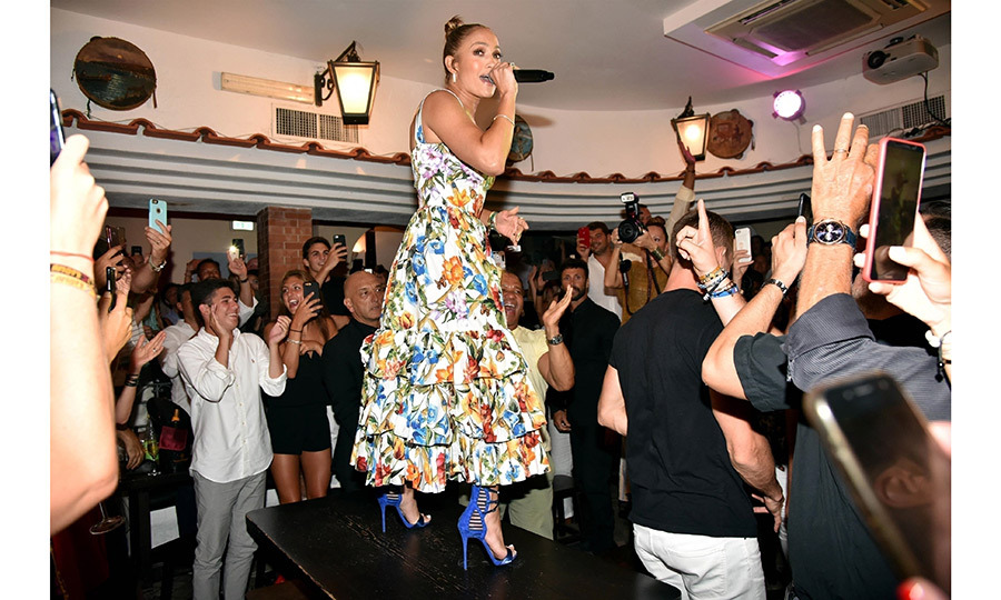"An impromptu concert? Why not! Jennifer Lopez made a table her stage in Capri on Aug. 8 while on vacation on the Amalfi Coast with her beau Alex Rodriguez. Wearing a floral dress and royal blue heeled sandals with her hear in a tight bun, the star sand ""Let's Get Loud"" while a crowd formed around her and danced their hearts out! 