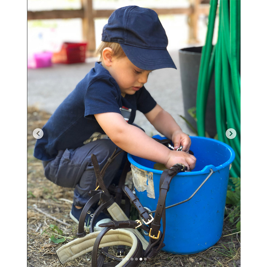 Adorable Prince Oscar got to work cleaning some straps from the pony. 