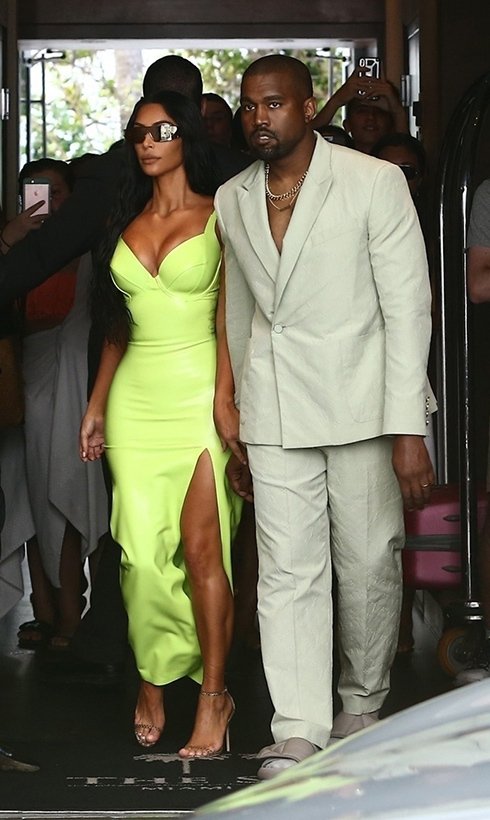 Lovebirds Kim Kardashian and Kanye West showed off their unique wedding guest looks on 2 Chainz's big day at the Versace Mansion.