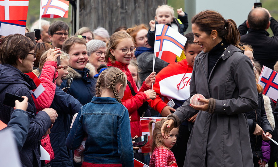 Princess Mary donned a black turtleneck, brown waterproof coat with a cinched waist and a ponytail while chatting with children in Hvalvik Island on the third day of the tour. 