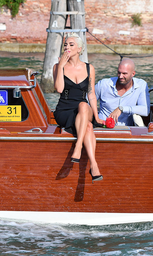 Lady Gaga has arrived in Venice!  The <em>A Star Is Born</em> lead made an ultra-glam appearance in a water taxi, perched on the edge blowing kisses to fans. The multitalented star wore a plunging black dress with corseted detail on the sides and black pumps with her blonde locks in a retro updo. Her highly anticipated film, co-starring and directed by Bradley Cooper, makes its world premiere on Friday (Aug. 31). 