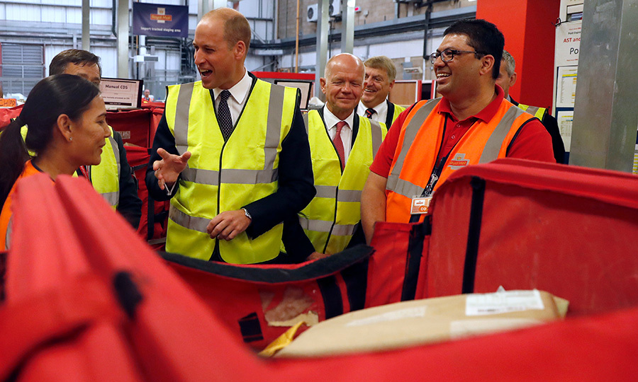 Fresh off summer holiday with his family of four, Prince William paid a visit to the Royal Mail international distribution centre near Heathrow Airport. The royal chatted with some sorting office workers, and later took a peek at some of the items not allowed into the UK – like snake skins and ivory products.