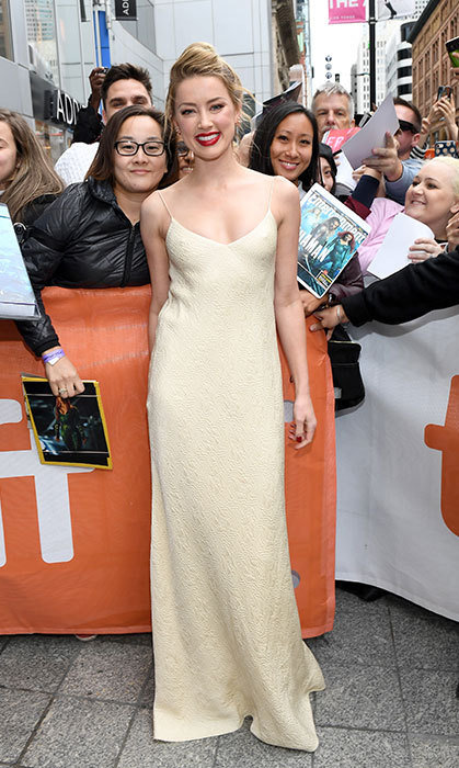 Amber Heard dazzled in an ivory gown as she posed with fans.
