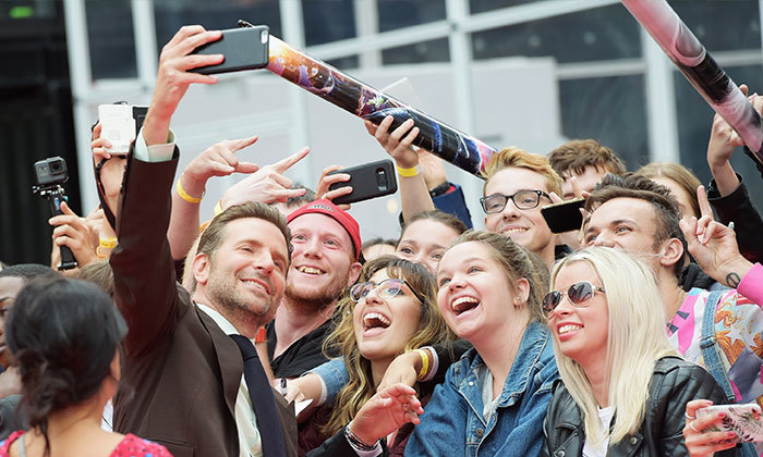 Bradley Cooper made sure to snap some selfies with his adoring fans on the carpet for <em>A Star Is Born</em>.