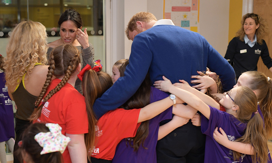 Prince Harry got a major group hug while visiting StarHub with his then-fiancee, Meghan.