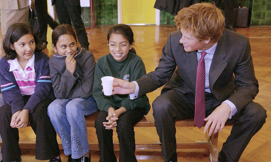At just 18 years old, Prince Harry paid a visit to The Osmani School in London. He passed a little girl – who looked a bit shy! – a cup of water.