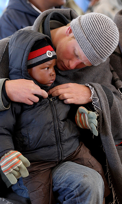 The prince helped fix this little boy's jacket during his visit to Lesotho in 2010.
