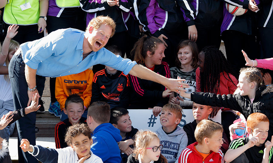 While in Scotland, Prince Harry reached over to hold hands briefly with a little girl. He's a popular guy!