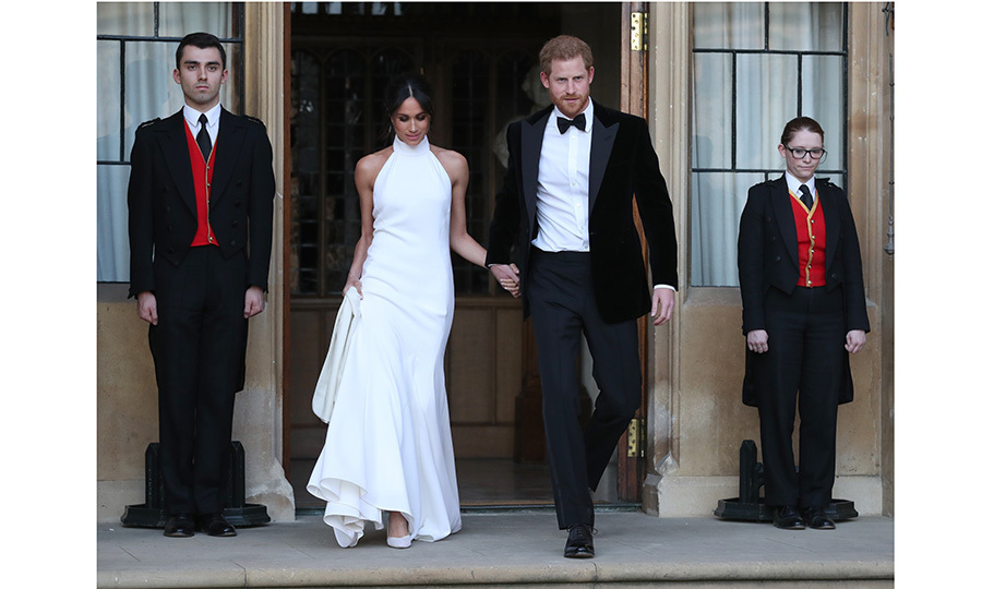 Prince Harry and Meghan traded their fairy-tale wedding gown and military uniform for James Bond-worthy ensembles as the dapper prince led his new wife to the passenger seat of a vintage Jaguar before driving them to their black-tie reception on May 19, 2018. (Photo: Steve Parsons - WPA Pool/Getty Images)