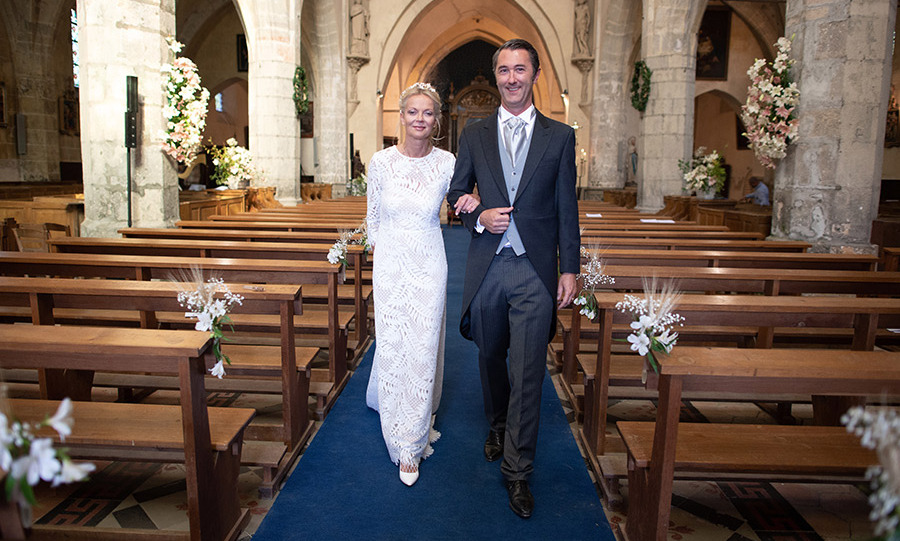 The bride and groom made a dashing pair as they posed on the blue aisle of the Saint Etienne de Janville church, which was decorated with beautiful blooms to match the bride's modest bouquet and floral headpiece. 