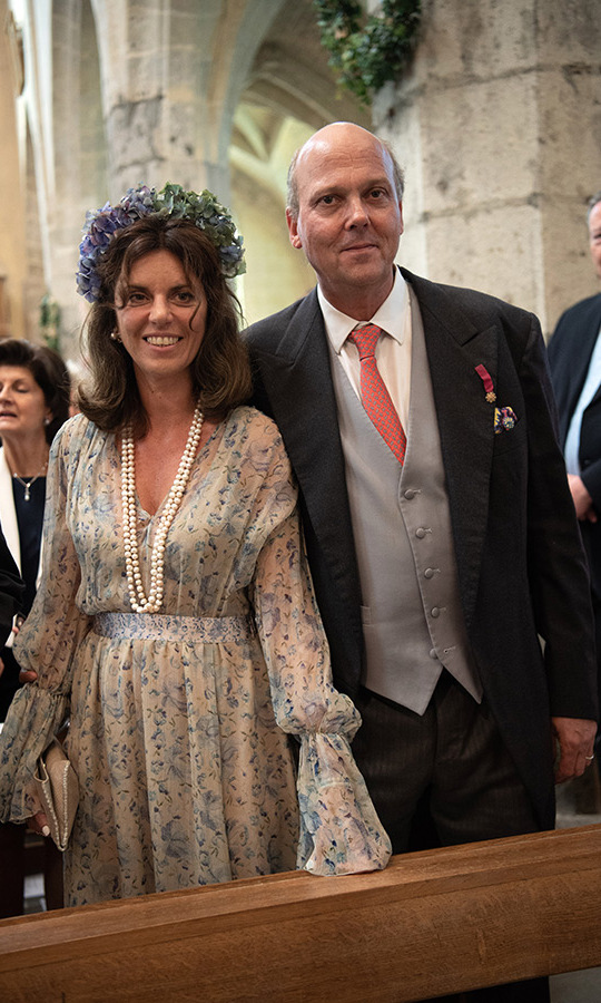 After accompanying his sister down the aisle, Prince Serge of Yugoslavia joined his wife Eleonora Rajneri in the pews. Eleonora looked beautiful in a printed gown with bell sleeves, pearls and an oversized floral garland. 