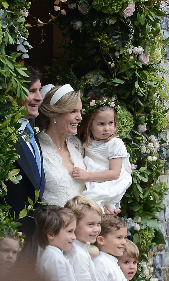 Sophie, who looked stunning in a classic white headband, lace-edged veil and white gown with a scalloped lace jacket, is one of Princess Charlotte's godmothers. William and Kate's middle child was clearly comfortable in her arms as her brother smiled sweetly for the camera.