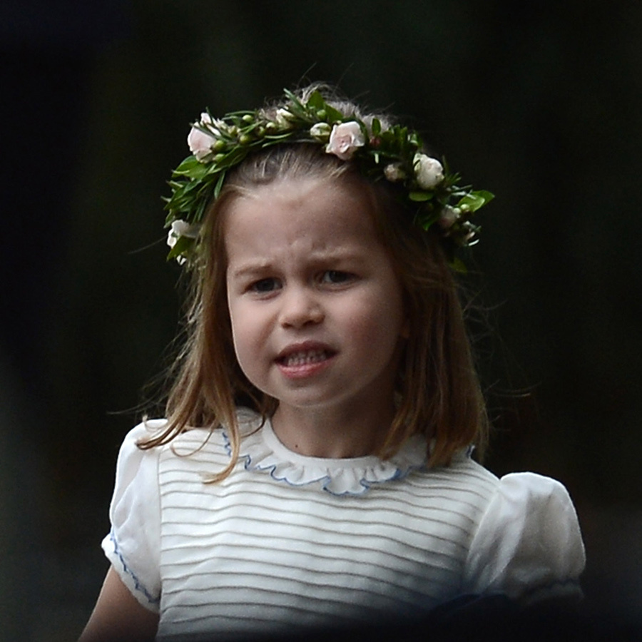 Princess Charlotte wore a pretty white dress with a ribbed bodice and ruffled collar piped in blue and puffy short sleeves. The three-year-old also wore a floral crown, which she'd done before at her aunt Pippa Middleton's wedding last year.