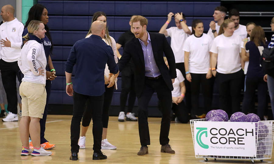 Prince Harry looked dapper as ever in a business casual outfit as he greeted officials on the basketball court.