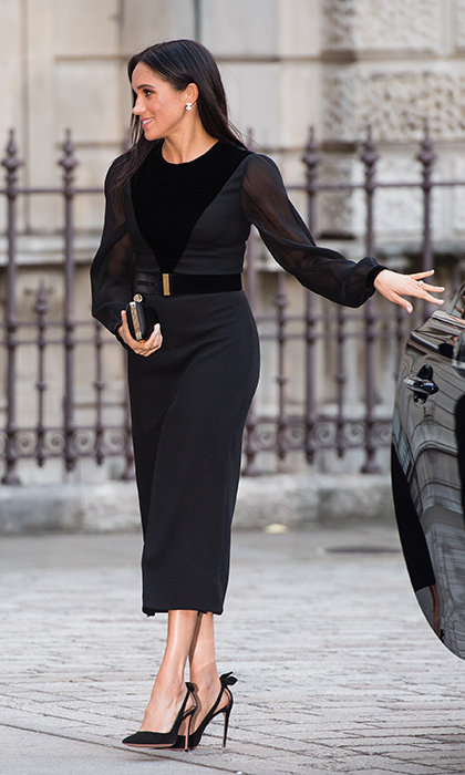 Meghan arrived looking every inch the fashion maven, showing off a new dress and recycled Aquazzura Deneuve Bow pumps.
