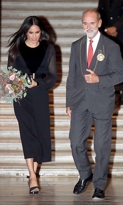 Meghan clutched a gorgeous bouquet of flowers while leaving the building.
