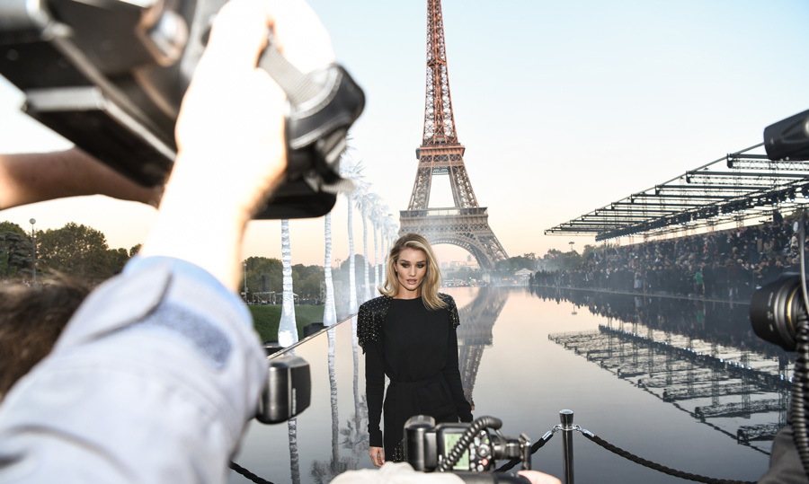 Rosie Huntington-Whiteley had quite the backdrop as she posed for photographers outside the Saint Laurent show during Paris Fashion Week.
