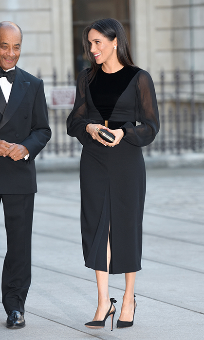 Meghan celebrated the beginning of autumn by helping open the <em>Oceania</em> exhibit at the Royal Academy of Arts in London. Staying true to her favoured luxury brand, the duchess dazzled in a black Givenchy dress, which boasted billowing sheer sleeves and a front slit. She accessorized with a satin Givenchy clutch, her Birks Snowflake earrings and her favourite pair of Aquazzura pumps.