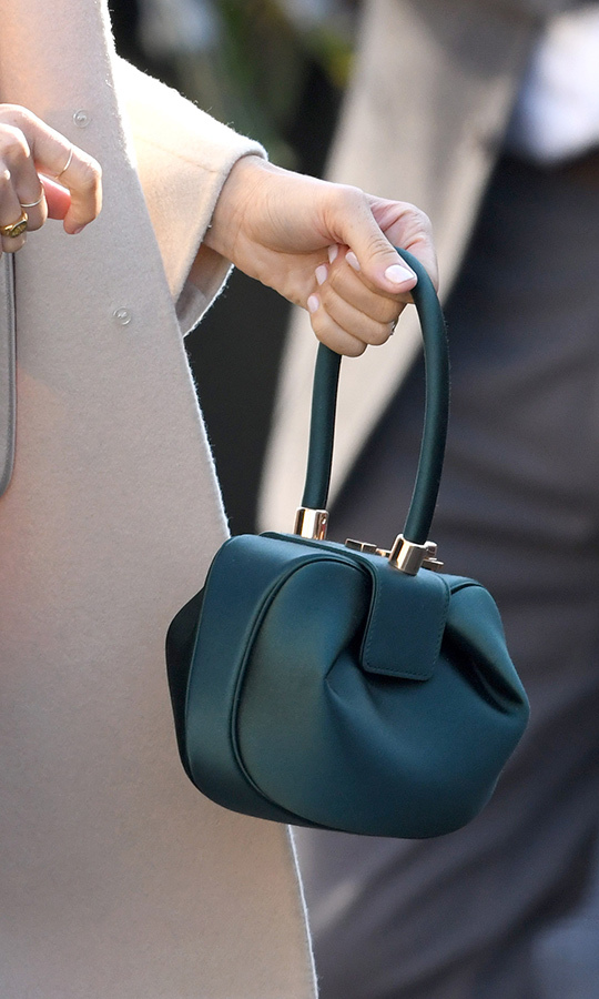 The duchess carried a $2800 Gabriela Hearst handbag with an interesting ball shape. The designer crafts her accessories from ninety-nine percent sustainable materials. 