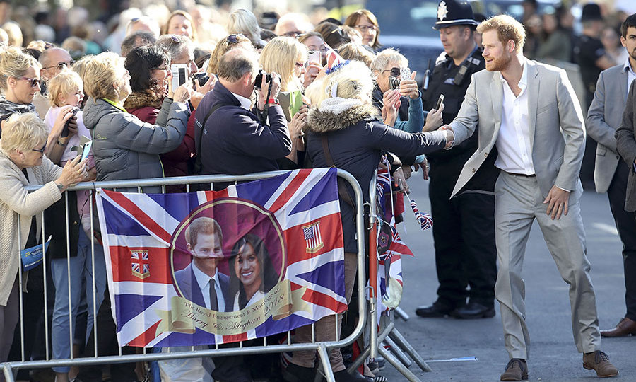 Prince Harry shook hands during a walkabout as a flag with the couple's engagement photo at its centre hung from the gates. 