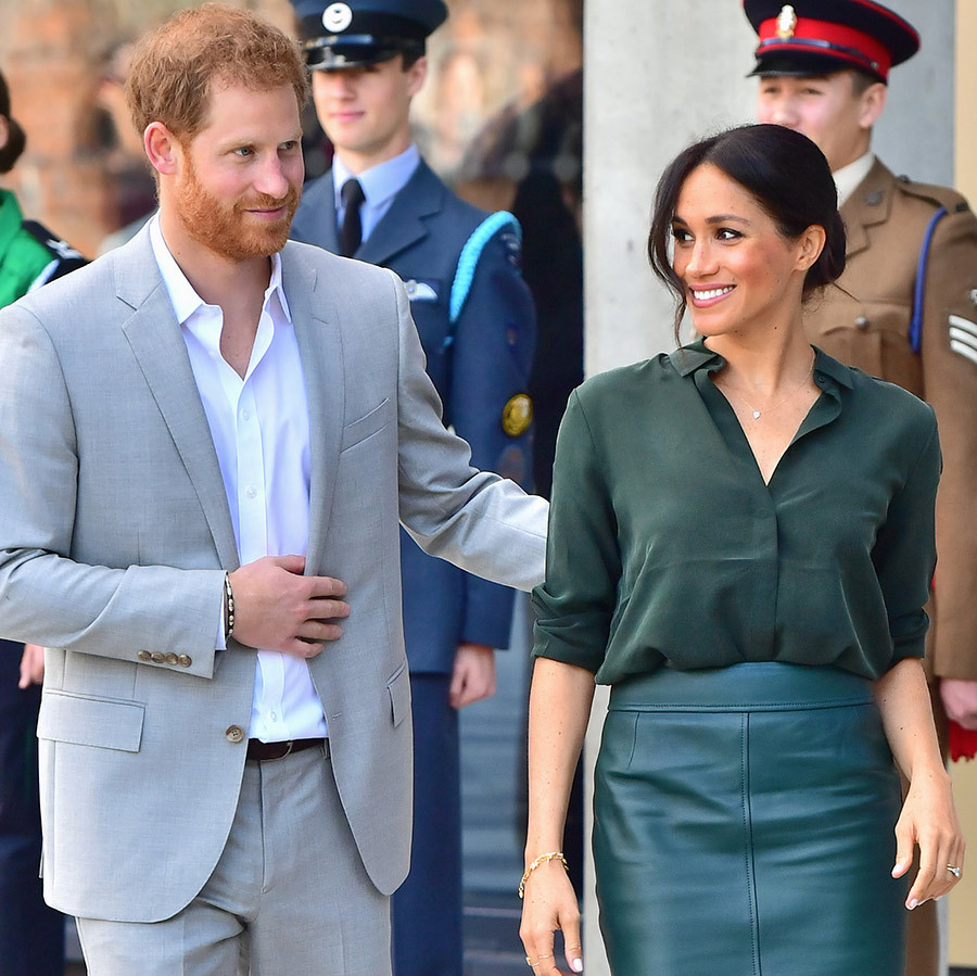 Prince Harry put a sweet arm on his wife's back as they walked.