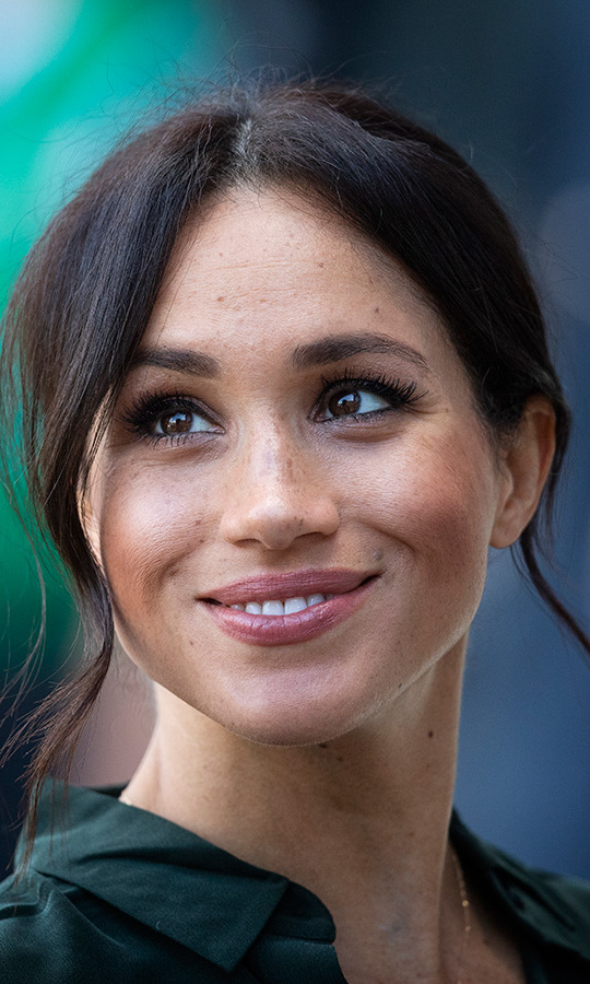 The former actress wore her hair in her signature relaxed bun with tendrils framing her face. Keeping her freckles front and centre and opting for a bronzy glow, Meghan looked natural while accentuating her pretty features courtesy of some eyeliner, mascara and a swipe of pink lipstick.