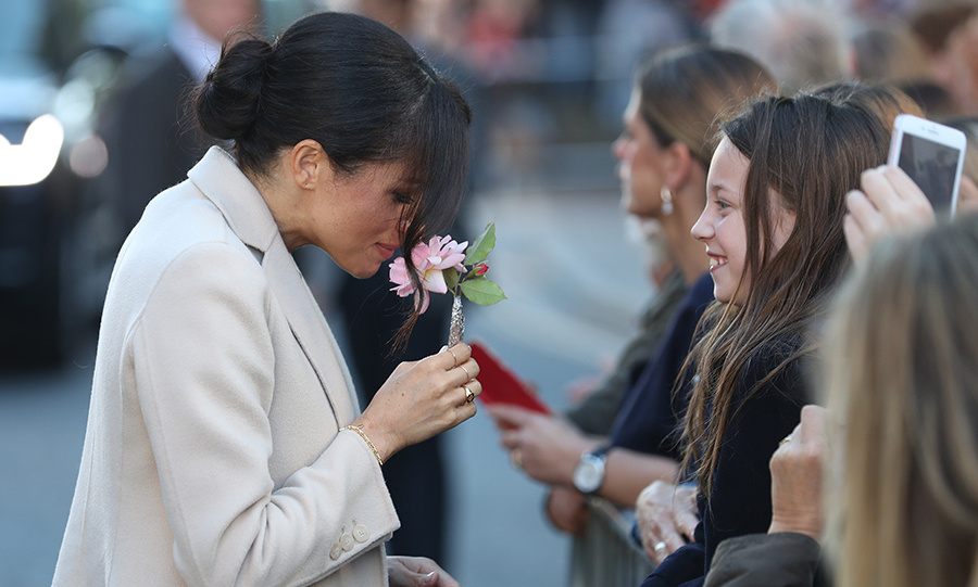When a young admirer handed her a flower, Meghan took a moment to enjoy its sweet scent!