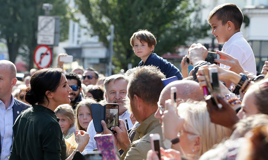 The royal greeted well-wishers outside the Royal Pavilion, including two sweet boys perched on their parents' shoulders.