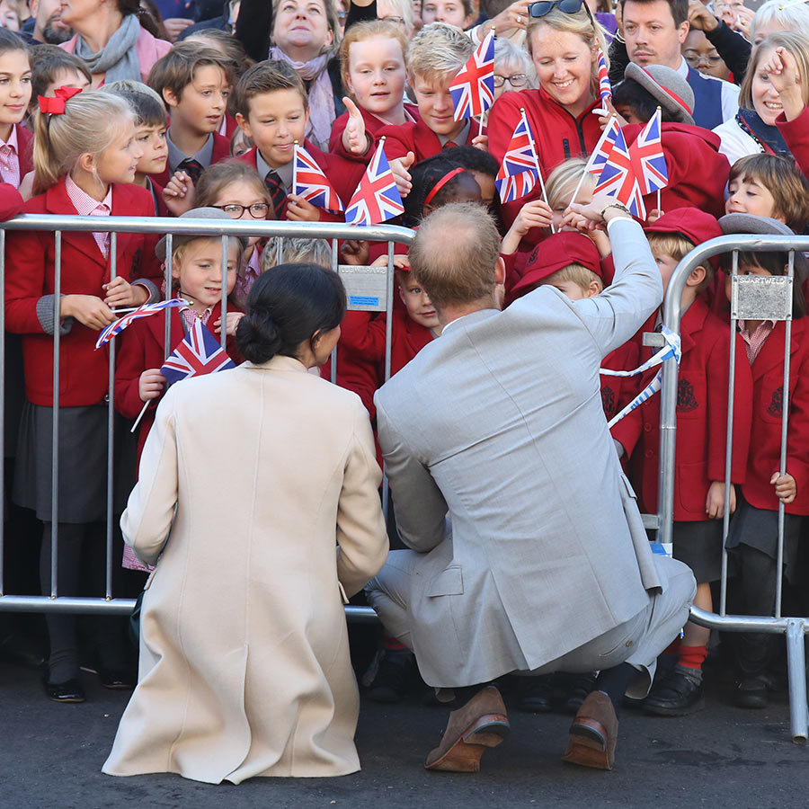 No matter where Harry and Meghan go, they always have a gaggle of kids eager to meet them! While visiting their namesake county of Sussex on Oct. 2, the two spent loads of time chatting with a group of school kids in their adorable red uniforms.