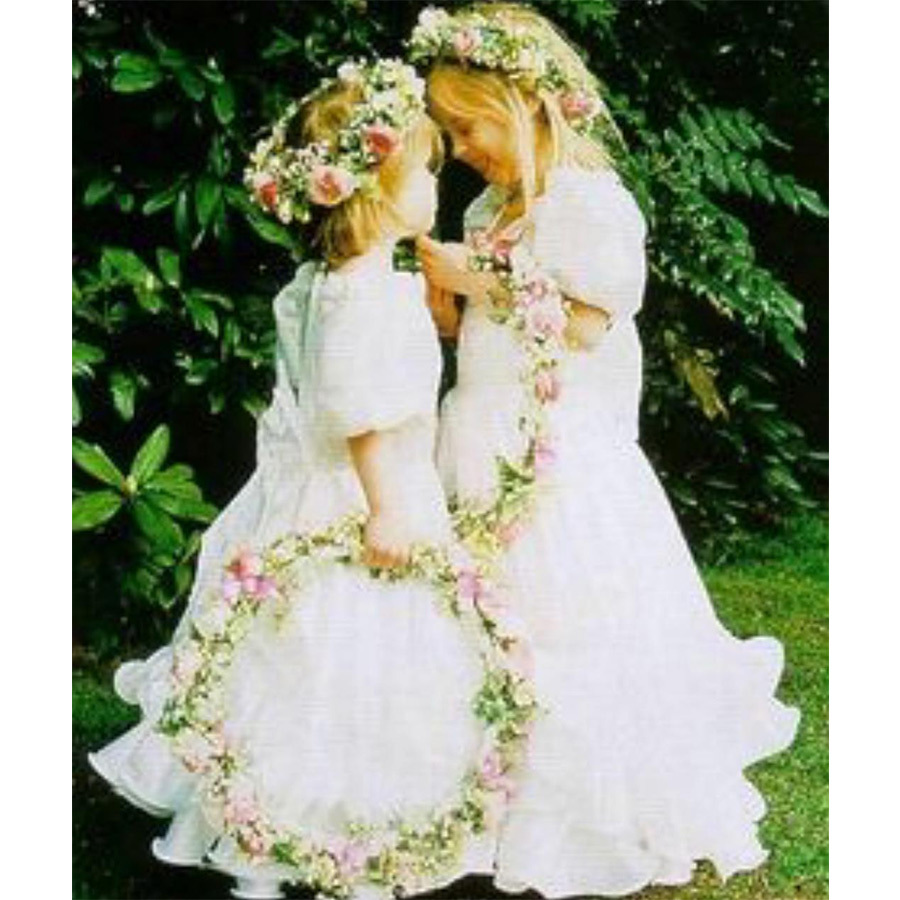 "Just one week before her royal wedding, Princess Eugenie shared this sweet throwback with her sister, Princess Beatrice, and the caption ""sisterly love."" Both clad in floral crowns and carrying rings of pretty blooms, the snap is fittingly from a wedding  - that of their former nanny, Alison Wardley, who had the adorable little girls as her bridesmaids when she married bodyguard Ben Dady in 1993. Will they don floral crowns again on Oct. 12?