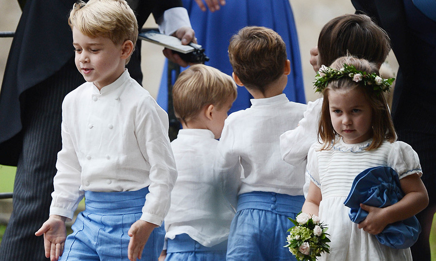 The Cambridge kids looked adorable in their bridal party outfits - George, 5, in blue shorts with a double-breasted, collarless white shirt and his sister Charlotte, 3, in a white short-sleeved dress with blue trim and scalloped hems. She topped off the look with a floral crown and carried a mini bouquet and a blue pouch (mom's purse?).