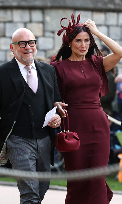 Demi Moore carried the same Gabriela Hearst bag that Duchess Meghan wore in Sussex, looking radiant in a burgundy dress and netted headpiece.
