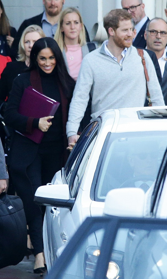 After a 22-hour flight that included a stop in Singapore, Meghan looked refreshed and excited as she arrived in Sydney, where the couple kicked off their 16-day tour. Clutching a binder full of notes, the newlywed wore a chic black coat with a burgundy lapel (the same one from an Invictus Games promo pic released a week prior), a black turtleneck, pencil pants and black pumps. She wore her hair sleek and straight with her signature natural makeup and a pink lip. 